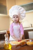 Little girl cuts dough for cookies on kitchen Royalty Free Stock Photo
