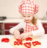 Little girl cuts dough with form for cookies Royalty Free Stock Photo