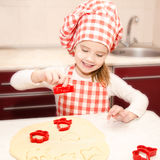 Little girl cuts dough with form for cookies Stock Photography