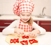 Little girl cuts dough with form for cookies Stock Photos
