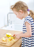 Little girl cutting apple. Royalty Free Stock Images