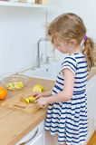 Little girl cutting apple. Stock Image