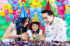 Little girl cutting birthday cake with parents Stock Images