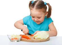 Little girl is cutting carrot for salad Royalty Free Stock Image