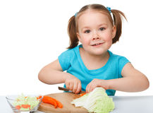 Little girl is cutting carrot for salad Royalty Free Stock Images