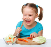 Little girl is cutting carrot for salad Stock Photography