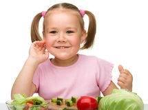 Little girl is cutting carrot for salad Royalty Free Stock Photo