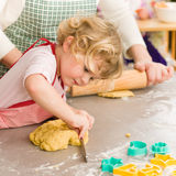 Little girl cutting dough for cookies. Little girl cutting out dough for cookies cute blond child Stock Photography