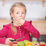 Little Girl Cutting Fruit In Kitchen Stock Images