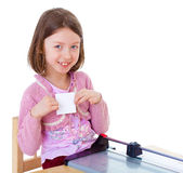 Little girl is cutting paper Stock Image