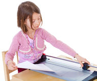 Little girl is cutting paper Stock Images