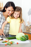 Little girl cutting vegetables with her mother Stock Photography