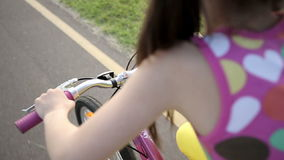 Little girl cycling in park on a pink bike. Slow motion.  stock video