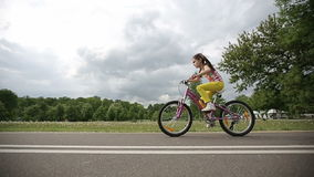 Little girl cycling in park on a pink bike. Slow motion. Dolly shot stock video footage