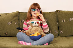 Little girl with 3d glasses eat chips Royalty Free Stock Images