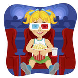 Little girl with 3d glasses holding popcorn sitting on chair in cinema Stock Photos