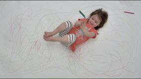 Little girl dabbles on camera on painted floor