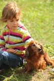 Little girl with dachshund sits on grass Stock Photography