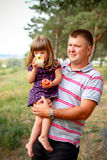 Little girl with dad in the forest, girl drinking milk and eatin Royalty Free Stock Photo