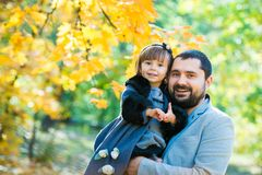 Little girl with dad playing in autumn park Royalty Free Stock Photography