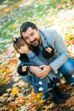 Little girl with dad playing in autumn park Royalty Free Stock Image