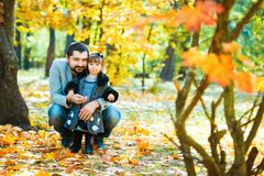 Little girl with dad playing in autumn park Stock Image