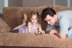 Little girl with dad playing on couch. Little girl with dad playing on the couch royalty free stock photos