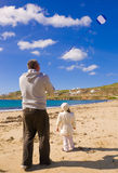 A little girl and dad run kite in sky with clouds Royalty Free Stock Images