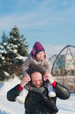 A little girl and dad run and play with the snow, lifestyle, winter holidays. A little girl and dad run and play with the snow royalty free stock image