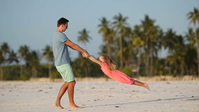 Little girl and dad during tropical beach vacation stock video