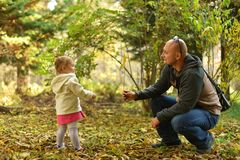 Little girl with dad walking in the forest in the autumn. stock photography