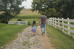 Little girl and dad walking on path stock photos