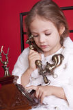 Little girl dails a number on phone Royalty Free Stock Images