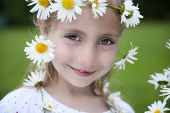 Little girl with daisies in her hair Stock Images