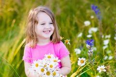 Little girl in daisy flower field Royalty Free Stock Photo