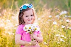 Little girl in daisy flower field Stock Image