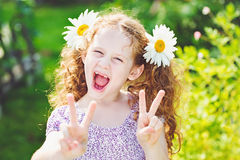 Little girl with daisy in her hair showing peace or victory hand. Triumph Stock Photography