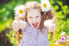 Little girl with daisy in her hairs, showing thumbs up. Royalty Free Stock Image