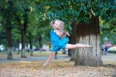 Little girl dancer jump in summer park. Child dance in blue dress, fashion. Happy childhood concept. Energy, activity, performance, ballet, gymnastics. Grace stock image