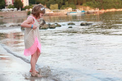 Little girl dancing on the beach with a beautiful dress Stock Image