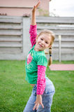 Little girl dancing. Blonde little girl dancing and having fun outdoors royalty free stock images