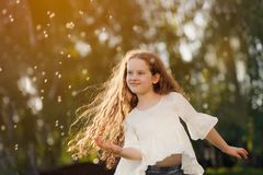 little girl dancing in flying dandelions outdoors Royalty Free Stock Image