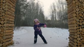 Little girl dancing funny dance on snow during winter walk in forest. Funny girl with tree branch dancing in winter forest stock video