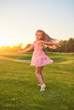 Little girl dancing on grass. stock photography