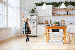 Little girl dancing on kitchen with Christmas decorations royalty free stock photography