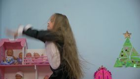 The Little Girl Is Dancing. Little caucasian white european active 5 years old girl with long hair is dancing in black penguin costume with pink bow tie in the stock video