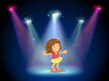 A little girl dancing in the middle of the stage with spotlights Royalty Free Stock Photos