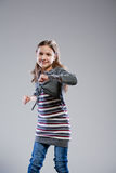 Little girl dancing on a neutral background Royalty Free Stock Photo