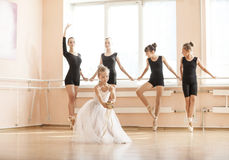 Little girl dancing with pointe shoes, older classmates warming up at the barres. Royalty Free Stock Photo