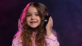 Little girl dancing on smoky background in headphones, slow motion stock footage